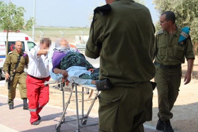 IDF officers escort injured Palestinian civilians for treatment at the IDF field hospital on the Israeli side of the Erez border crossing with the Gaza Strip on July 21, 2014. (IDF/Flickr)