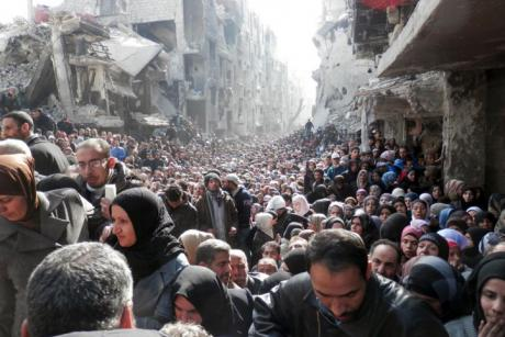 Refugees wait in line to receive food aid distributed in the Yarmouk camp on January 31, 2014 in Damascus, Syria. (United Nation Relief and Works Agency – UNRWA)