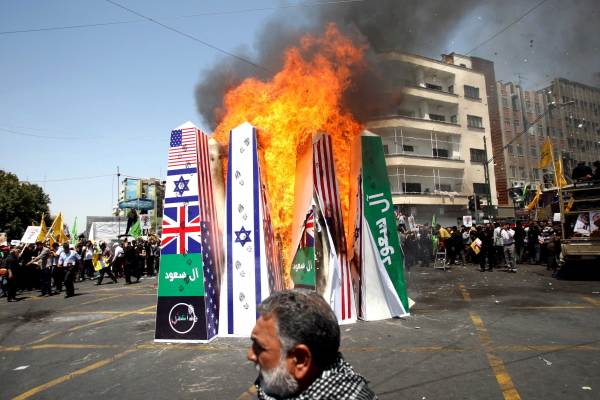 "Iranian demonstrators burn symbolic structures of its archenemies depicting the flags of the U.S., Britain, Saudi Arabia , Islamic state and Israel during a rally marking the international al-Quds (Jerusalem) Day in Tehran July 10, 2015. The green banner reads, ""Saud family,"" referring to the royal family of Saudi Arabia. REUTERS/Stringer/TIMA"