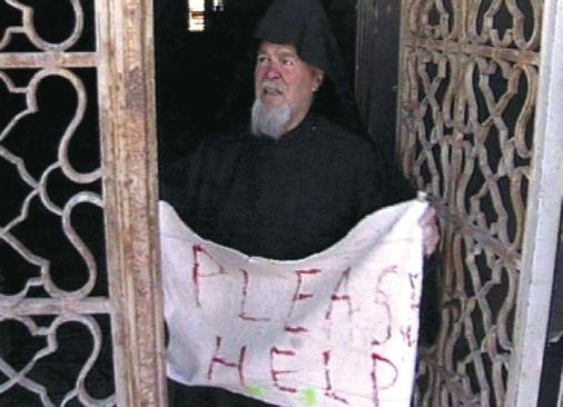 """A Greek Orthodox priest, held hostage by Palestinians who took refuge in the Church of the Nativity in Bethlehem, is holding a sign saying """"PLEASE HELP,"""" April 2002. (Government Press Office)"""