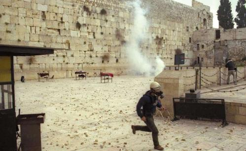 The Western Wall plaza is strewn with rocks that were thrown from the Temple Mount at Jewish worshippers. A policeman flees the scene. (Government Press Office)