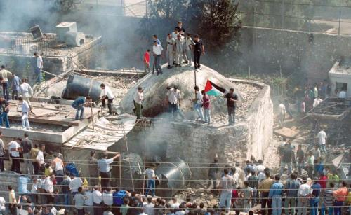"""Palestinians stand on the roof of Joseph's Tomb in Nablus on October 7, 2000, after Palestinian fighters and civilians had stormed the Israeli enclave, destroyed holy books, and set the sacred site on fire in a victory """"celebration"""" held a few hours after the IDF evacuated the site. (AP photo/Lefteris Pitarkis)"""