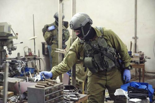 Israeli soldiers examining a weapons factory on the West Bank.