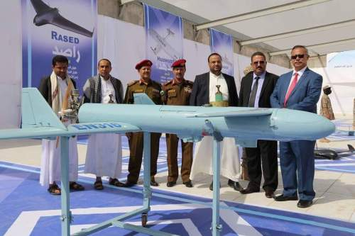 Houthi political-military leadership standing behind Qasef-1 attack drone.