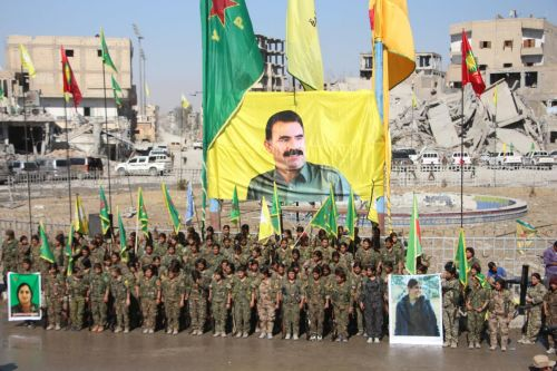 PKK women soldiers in Raqqa beneath a poster of PKK leader Abdullah Öcalan