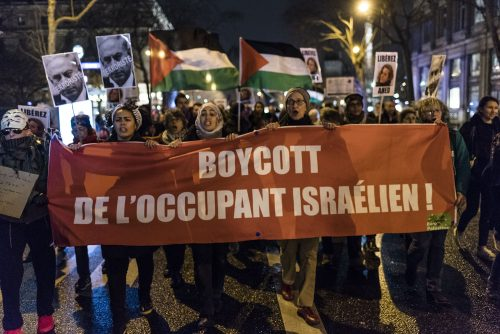 "Protesters hold a ""Boycott the Israeli occupant"" banner"