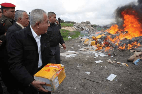 Salam Fayyad throws a package into a fire set to burn products from Jewish settlements