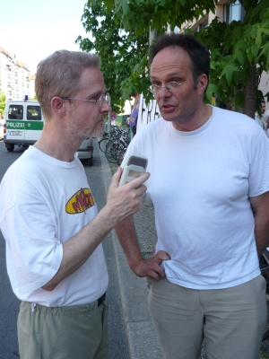 Martin Forberg (right) being interviewed during a demonstration opposite the offices of the German weapons manufacturer Rheinmetall.