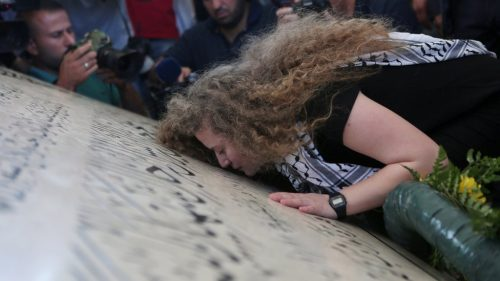 Tamimi kissing Arafat's grave in Ramallah after her release.