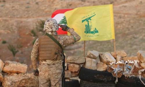 Hizbullah fighter saluting the Hizbullah and Lebanese flags