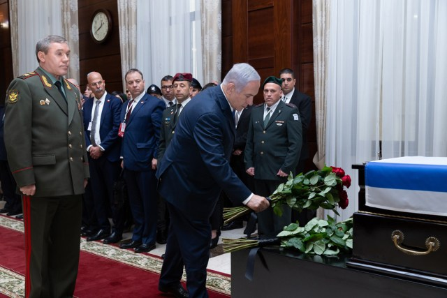Israeli Prime Minister Benjamin Netanyahu and Russian Chief of the General Staff Valery Gerasimov place roses on the casket containing Zachariah Baumel's remains