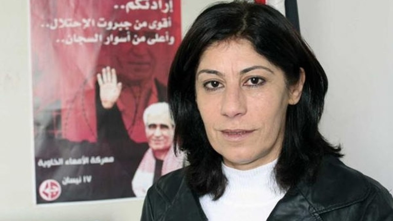 Khalida Jarrar posing with PFLP poster featuring the imprisoned terrorist Ahmad Sa'adat, convicted of plotting the 2001 murder of Israeli Tourism Minister Rehavam Ze'evi
