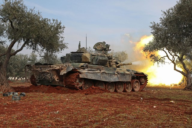 Syrian rebel fighters fire from the captured Russian T-90 tank