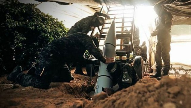 Hamas fighters loading a heavy rocket in an underground silo under camouflage