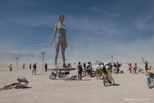 People gather around R-Evolution: The Woman Stands. The third and final sculpture in a series by Marco Cochrane.