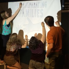 """Emily, Ellory, Noah and Emily create a banner for an upcoming """"Stop Deportations"""" rally as part of their project with the Illinois Coalition for Immigrant and Refugee Rights."""