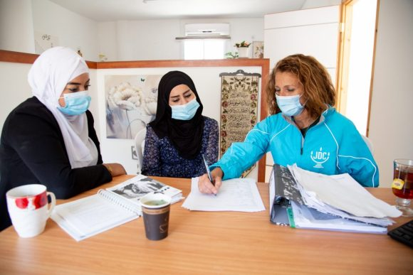 Ziva (right) sits with two Arab Israeli women, helping them fill out forms.
