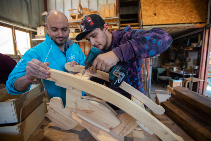 JDC volunteer in Israel helps young man in baseball hat with woodwork.