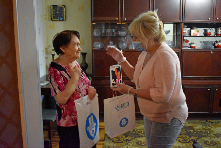JDC volunteer in the former Soviet Union holding a JOINTECH bag with an elderly female client in her kitchen.