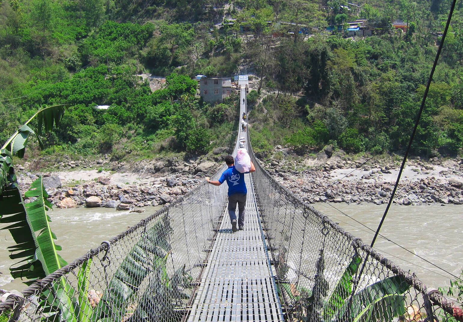 JDC aid worker carrying a large white package over his shoulder while crossing a rope bridge.