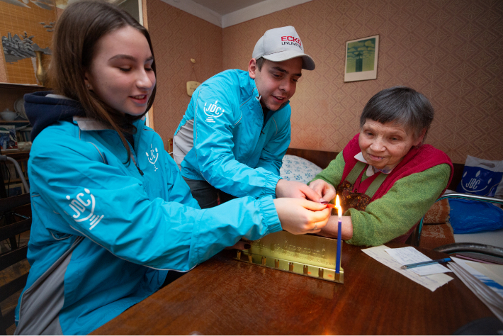Two young JDC volunteers in the former Soviet Union light Channukah candles with an elderly client in her living room.