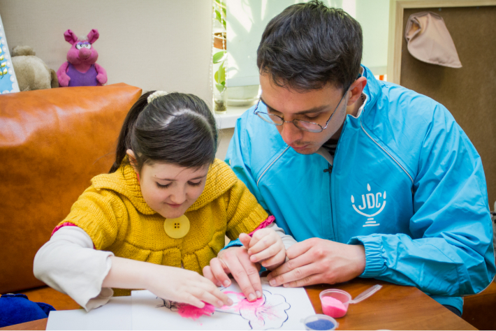 JDC volunteer in the former Soviet Union helping a young girl draw a pink flower.