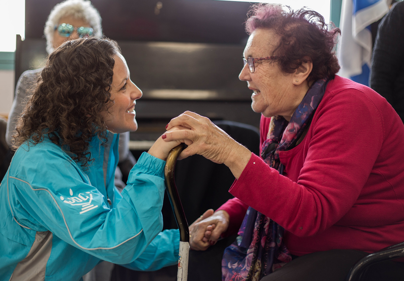 A JDC volunteer speaks to an elderly Holocaust survivor at a Cafe Europa event in Israel.