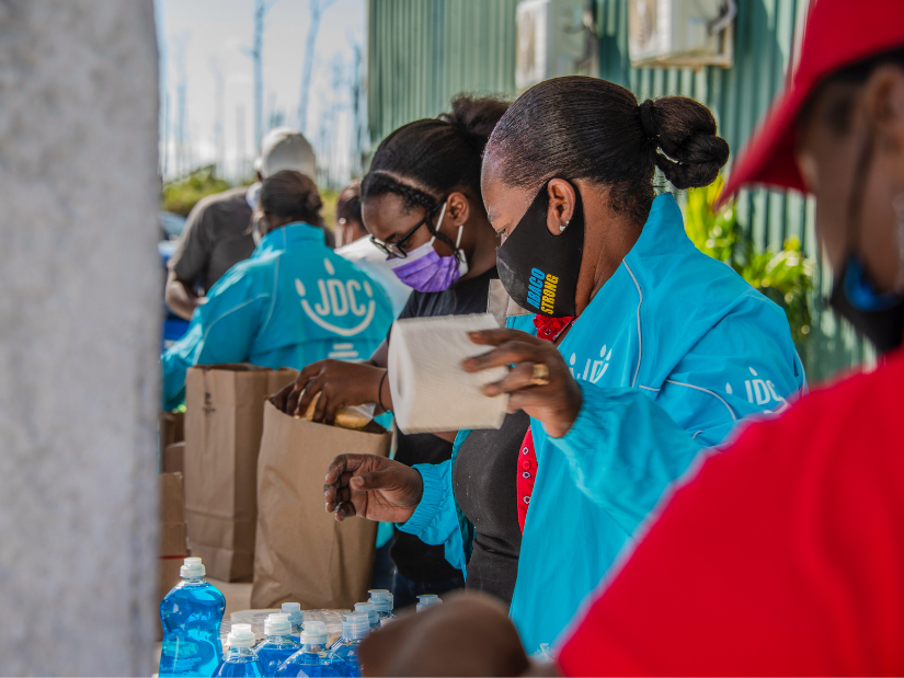 A JDC humanitarian aid workers in the Bahamas dispensing toilet paper and dish soap to victims of Hurricane Matthew.