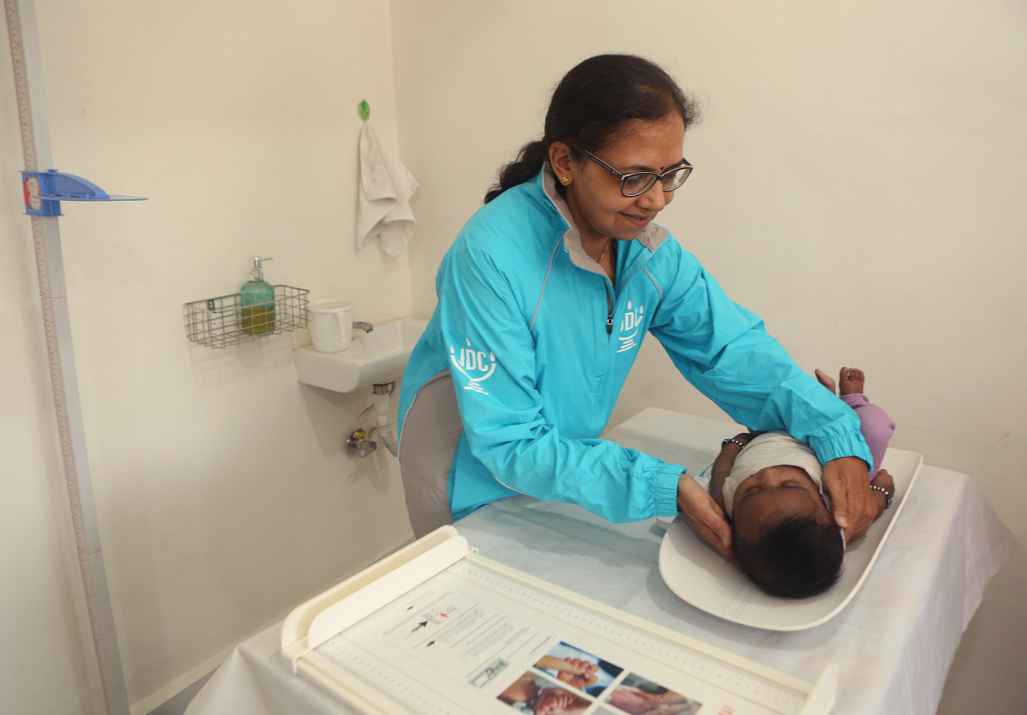 JDC medical volunteer placing a baby on a doctor's table in India.