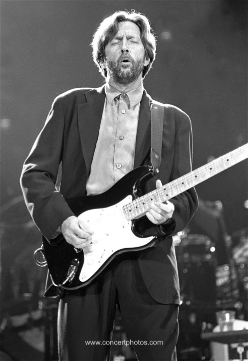 "Musician Eric Clapton is shown performing on stage during a ""live"" concert appearance."