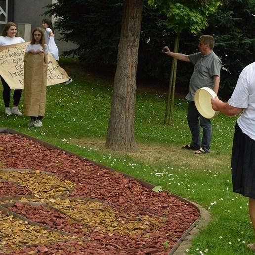 Teren zielony przed jasielskim domem kultury. Na trawie stoją dwie kobiety ubrane w białe koszulki, jedna z nich ma czarną spódnicę i jasne buty, druga czarne spodnie i jasne buty. Obok nich, w tele niewysoki mur z napisem JDK-jasielski dom kultury. Przed murem stoi męzczyzna ubrany w szarą koszulę i ciemne spodnie oraz sandały, robi zdjęcia młodym ludziom. W tle trzy dziewczyny ubrane w białe koszulki, czarne spodnie oraz chłopak ubrany tak samo, jak one. Jedna z dziewczyn trzyma rozwinięty, zapisany szary papier, stojący obok chłopak również. Druga dziewczyna z blond włosami owinięta jest szarym papierem, a trzecia tańczy