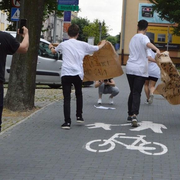 Ścieżką rowerową idzie grupa młodych ludzie, niosąc szary, potargany przez wiatr papier z cytatami Baczyńskiego. Zmierzają w stronę słupa ogłoszeniowego. Za nimi podąża mężczyzna i nagrywa akcję telefonem komórkowym. Na drodze namalowany biały rower