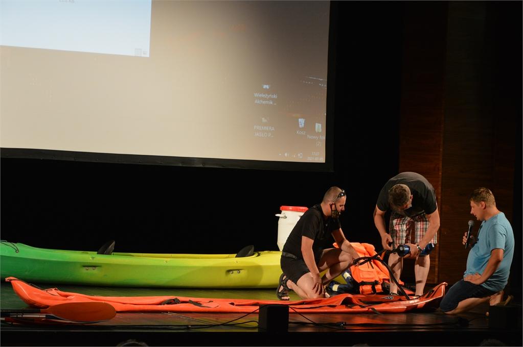 Dówch ochotników napompowuje kajak na scenie JDK pod okiem gościa 15. Klubu Ludzi z Pasją