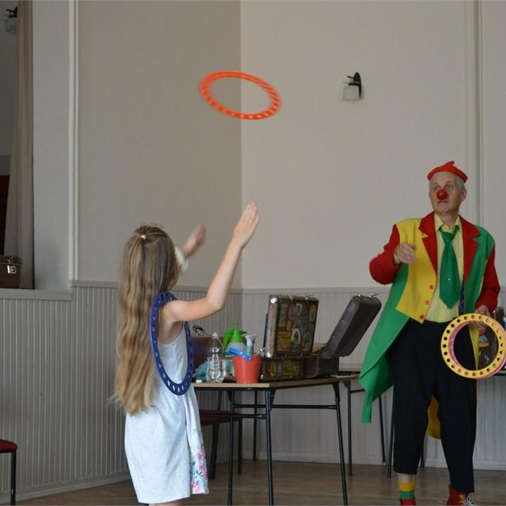 Dziewczynka łapie korową obręcz rzucona jej przez klauna Feliksa.