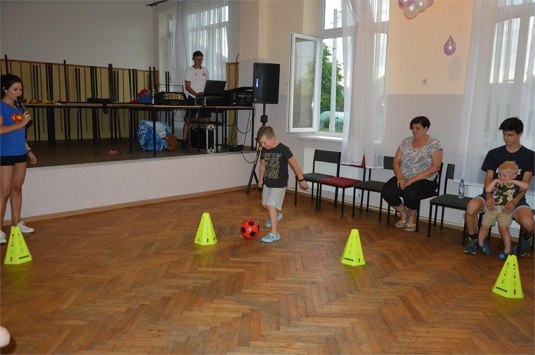 Chłopiec kopie piłkę między pachołkami. Z lewej strony stoi animatorka zabawy z mikrofonem. W tle podest ze stolikami i DJem.