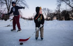 Benjamin Sapaugh lines up a pass as his father Stephen Sapaugh points to the person he should pass it to at University Park in Grand Forks, ND. Stephen said this was the first time Benjamin has taken to the ice with a hockey stick. (Joshua Komer / Grand Forks Herald)
