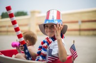 Ethan Edvall sits in a cart waiting for the parade to start in downtown Grand Forks, ND on July 4, 2015.