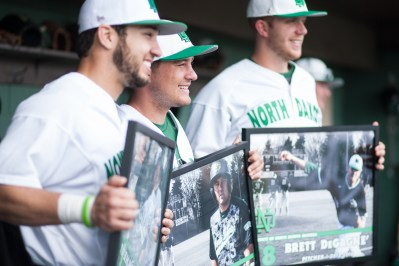From left, Luis Calvo, Daniel Lockhert, Brett DeGane' pose for photos while holding their commemorative pictures after their final game at Kraft Field in Grand Forks, ND on Sunday, May 15, 2016. (Joshua Komer/Grand Forks Herald)