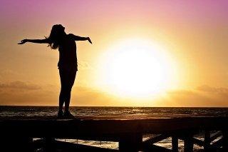 Cancer du sein : Femme ouvrant les bras au soleil et à la mer. Liberté retrouvée.