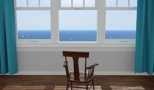comment vis-tu le confinement ? chaise installée devant une fenêtre avec une vue sur la mer