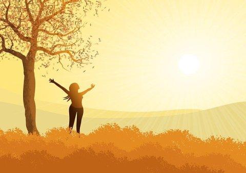 Lâcher prise - trouver la force en soi - Femme à côté d'un arbre ouvrant les bras vers le ciel