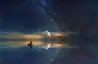 Dale Carnegie : « La personne qui va le plus loin est généralement celle qui est prête à agir et à oser. Le bateau sans risque ne s'éloigne jamais de la rive. » - Bateau navigant sous le ciel étoilée se reflétant dans la mer