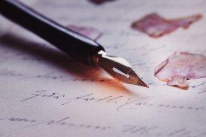 Stylo plume posé sur une page écrite où se trouvent quelques pétales de fleurs