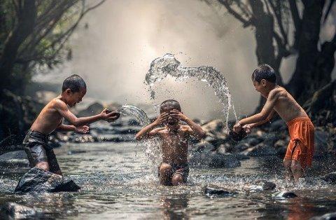 Carpe diem - enfants profitant de l'instant présent en s'éclaboussant dans une rivière