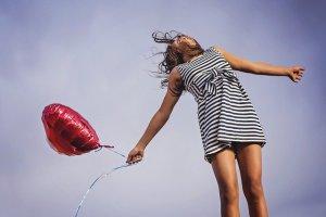 Le small talk rendrait heureux selon des études - petite fille en robe rayée sautant en l'air un ballon rouge à la main