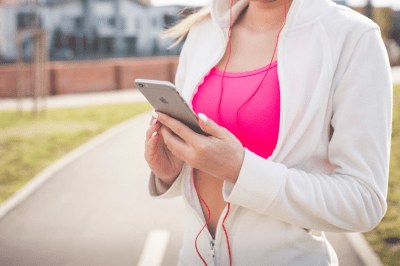 Lady wearing a pink sports bra and white jacket holding an iPhone.