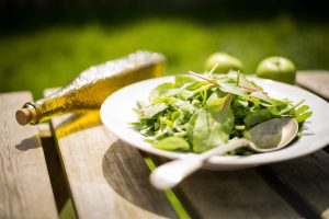 salad and olive oil on wooden table outside.