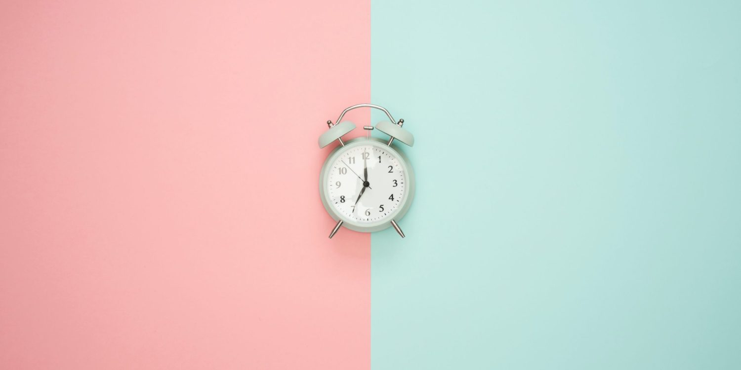 clock on pink and mint green background