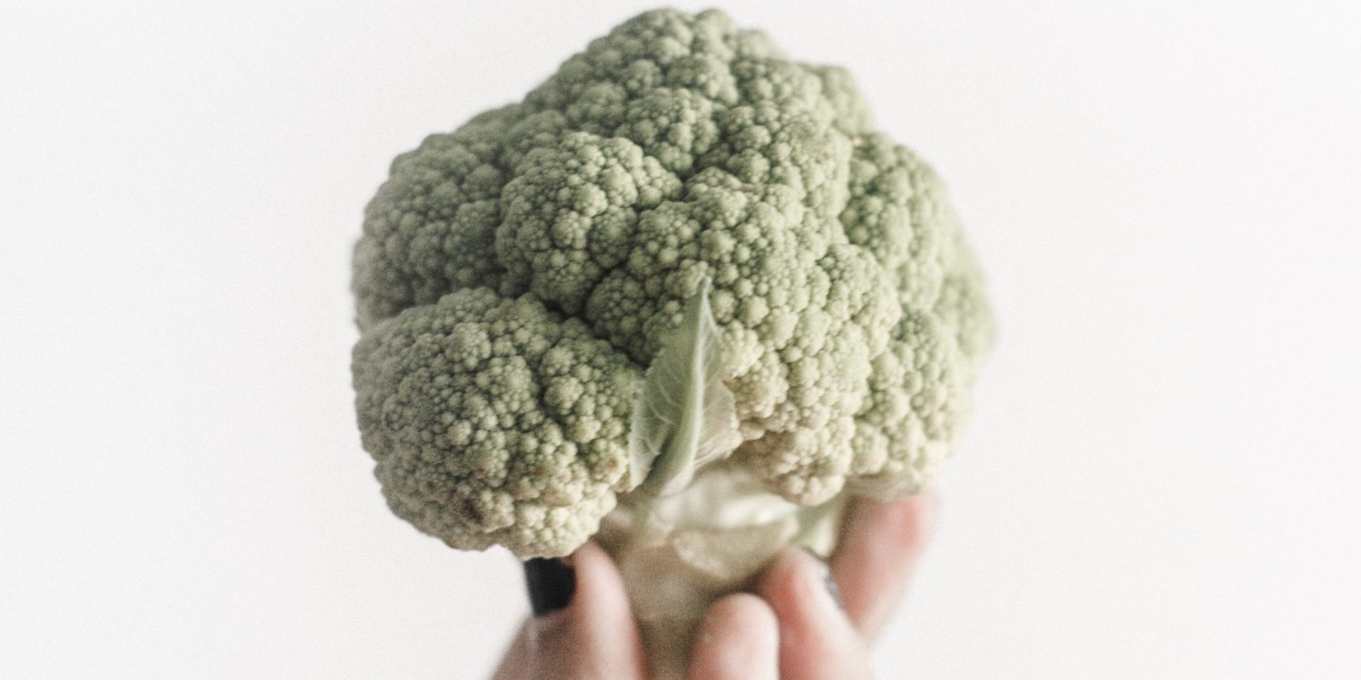Cauliflower being help up by a hand with white background