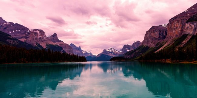 lake with mountains on either side and pink sky.